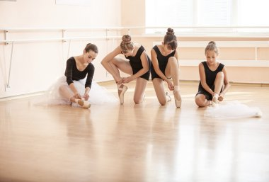 Young ballerinas putting on pointe shoes