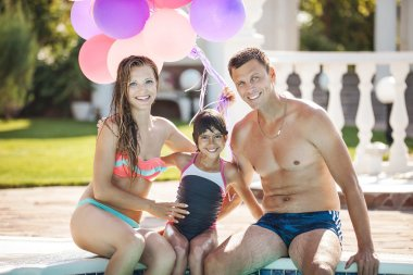 Happy family near a swimming pool