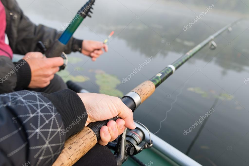 Close-shot of human hands holding a fishing-rod on the foregroun