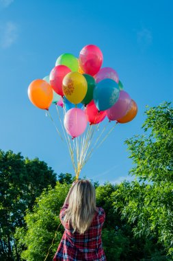colorful latex balloons in hand of young woman, outdoors