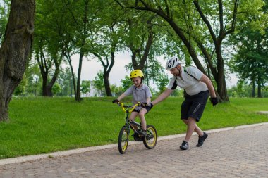 Father and son learning to ride a bike in the park having fun to