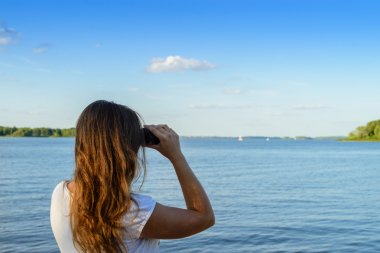 Woman looking through binoculars as a for a bright future, lands