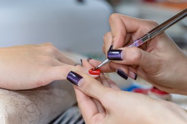 painting nails in nail salon, UV lap of quick dry nail polish ma