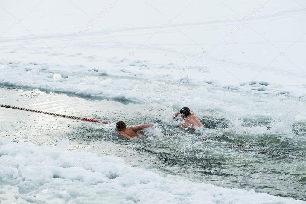 Ice swimming, swimming competitions in the winter outdoors at a frozen  lake. Extreme fitness sport. — Stock Photo © smspsy #97201888