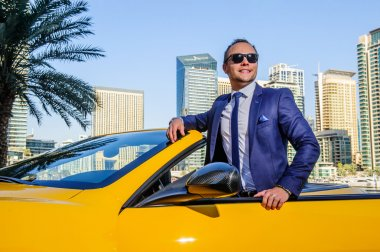 Successful yang businessman in yellow cabrio car