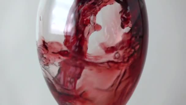 Red wine being poured into a glass against gray background, super slow motion