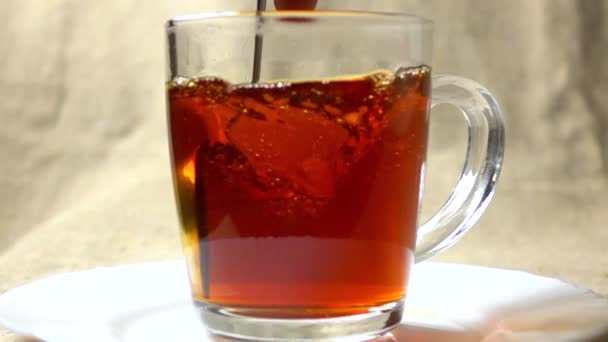 Super slow motion video of stirring black tea in a glass cup