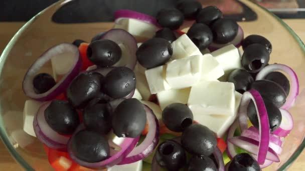 Odlévání olivový olej na řecký salát ve skleněné míse. Součást sady
