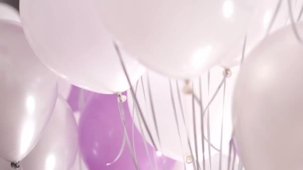 Mnoho bílé, růžové a stříbrné helium balóny vznášející se v místnosti