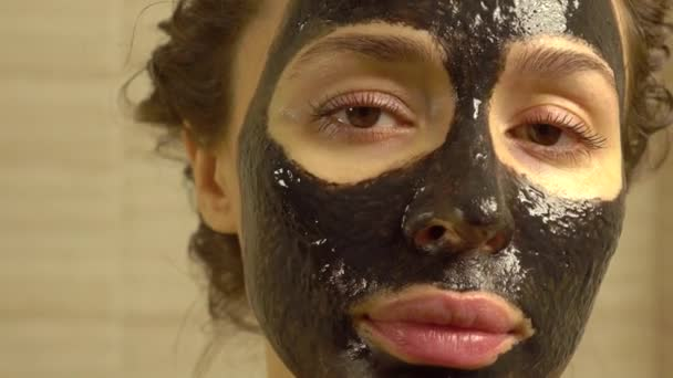 Beautiful young woman with cosmetic black face pack on her face. 4K close up