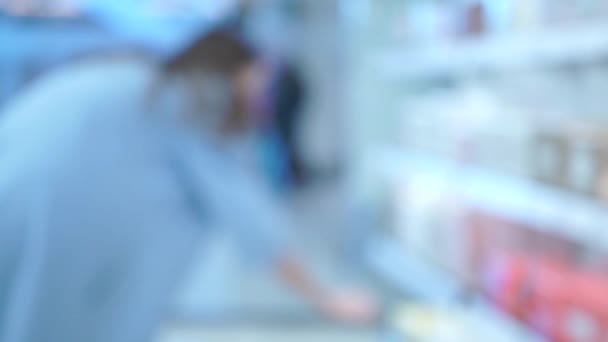 Blurred bokeh shot of young woman choosing perfume in a fragrance department
