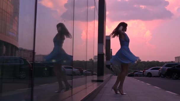 Slim girl in blue dress dancing on the street at pink sunset, super slow motion shot, 250 fps