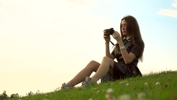 Beautiful brunette girl in black dress sitting on the lawn and making photos with her camera. Leisure time. 4K video