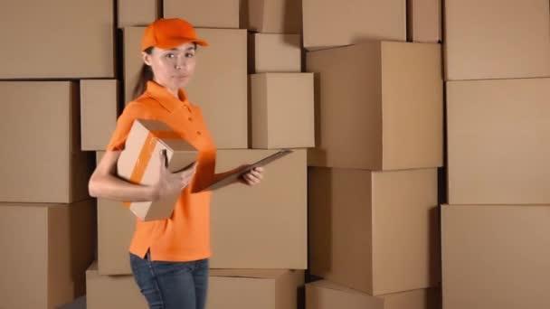 Krásné ženské courier v oranžové uniformě přináší balík proti krabičce hromádky pozadí. video 4 k studio