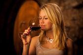 Schöne junge blonde Frau Verkostung Rotwein in einem Weinkeller