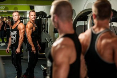 Twin brothers looking in mirror after body building workout in f