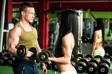 Fitness youple workout - fit mann and woman train in gym