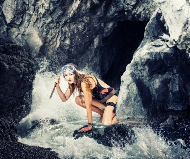 Adventure. woman with a knife in sea cave
