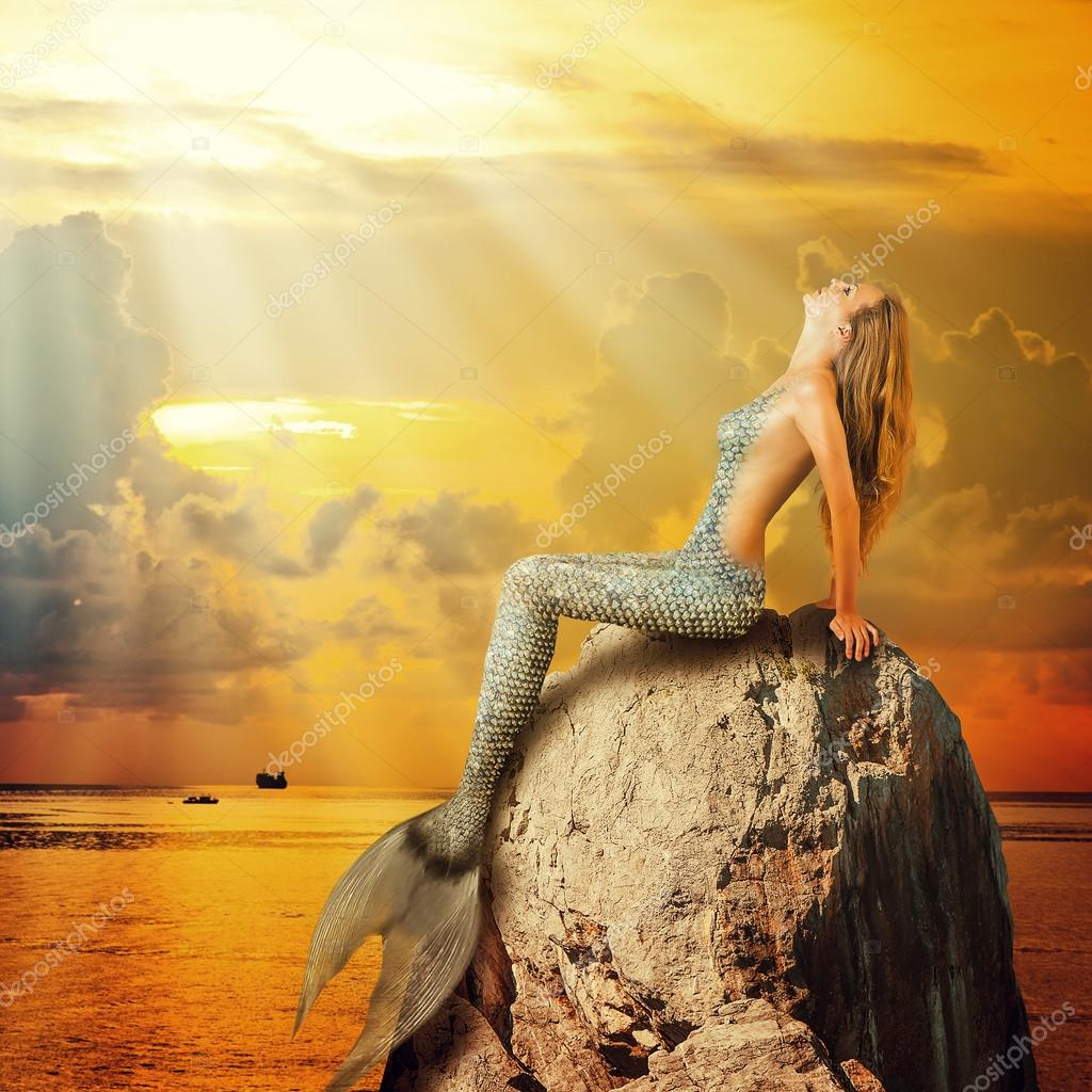 beautiful mermaid sitting on a rock