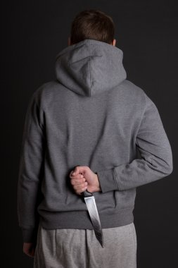 man hiding knife behind his back over grey