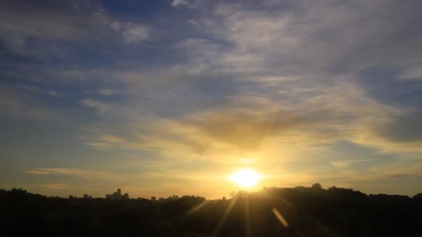 A naplemente és a felhők közötti időeltolódás és a felhőkarcolók sziluettjei a horizonton
