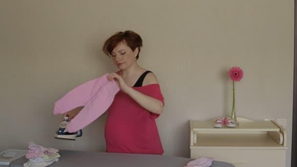 těhotná žena žehlení oblečení