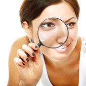 žena dívá skrz zvětšovací sklo