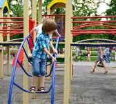 Junge spielt auf Spielplatz