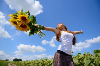 Young beautiful woman enjoying summer, youth and freedom, holding sunflowers above head, against blue sky stock vector