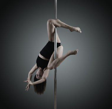young woman dancing on pylon