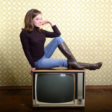 smiling woman sitting on retro tv