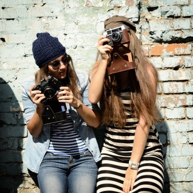 Urban girls have fun with vintage photo cameras outdoor near grunge wall, image toned and noise added stock vector