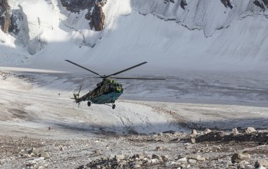 Military helicopter landing on ice of  mountain galcier in Ala Archa National Park (Kyrgyzstan)