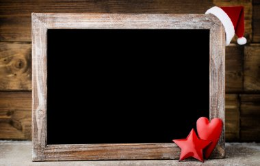 Christmas chalkboard with decoration. Santa hat, stars,  Wooden