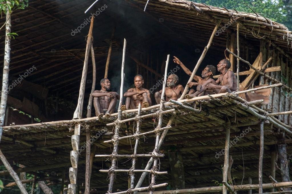 Group of Papuan Korowai tribe in house on tree