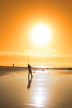 lone fisherman fishing on the sunset beach