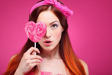 Portrait of beautiful  merry redheaded girl with a large candy on a pink background
