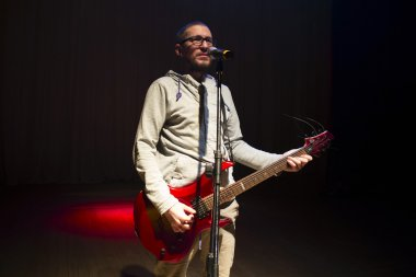 Man staying on stage and playing electric guitar