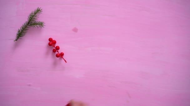 Mans Hand füllt weihnachtlichen rosa Hintergrund mit Tannenzweigen, Holunderbeeren und Weihnachtskugeln