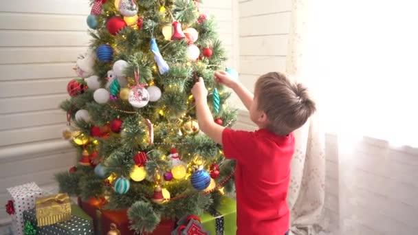 Junge schmückt Weihnachtsbaum in einem hellen, sonnigen Raum