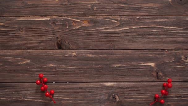 Mans ručně plní dřevěné vánoční pozadí s jedlovými větvemi, bezinky a vánoční míče