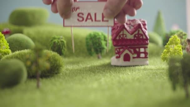 Sign house Na prodej v oblasti se zelenou trávou, stromy a kopci