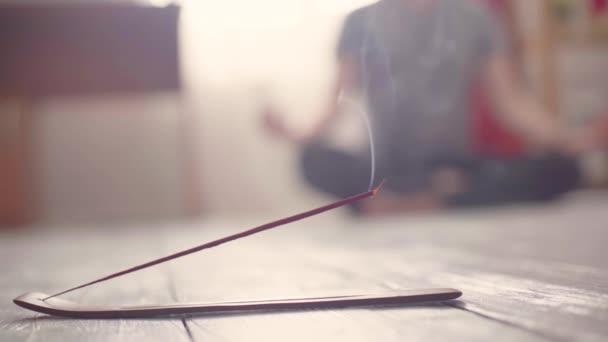 Dampfende Räucherstäbchen in Großaufnahme auf dem Boden und Yogi im Hintergrund