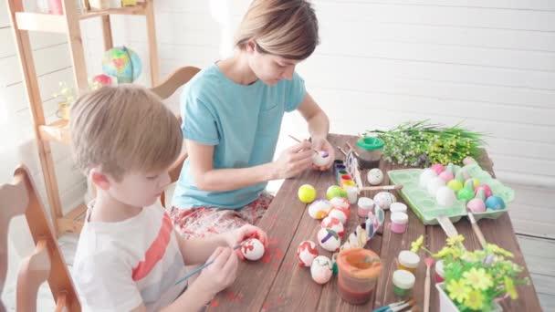 Frohe Ostern. Familie mit Kindern bemalt Eier für Ostern
