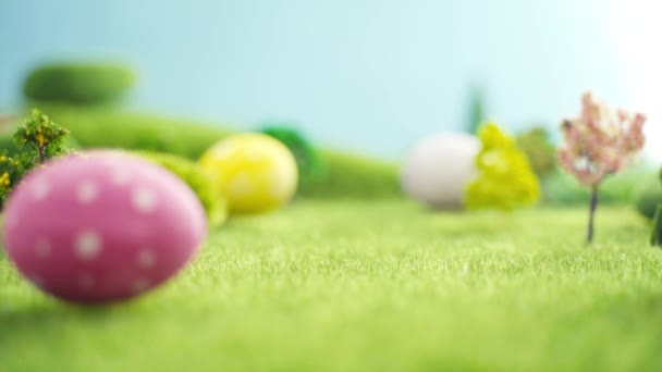 Hand laying easter egg on grass in fairytale fictional macrocosm