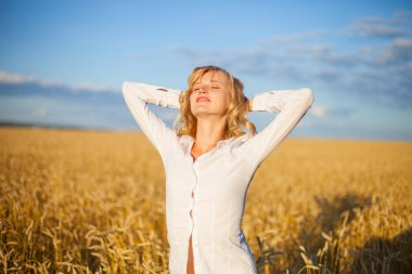 Young woman has pleasure time in grain field
