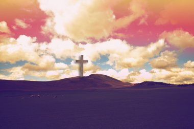 The Cross of Jesus Christ on the hills and dramatic clouds