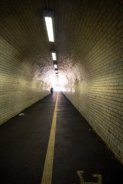 Silhouette of a man in a street tunnel.