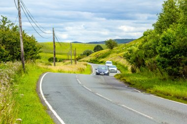 Winding road in the hills of Scotland with cars, sunny sumer day
