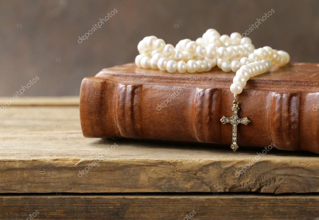 f0dad031dc1c Viejo libro (Biblia) y el símbolo cristiano cruzan en collar de perlas —  Foto